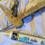 caulking gun and tube for filling gaps around windows and baseboards