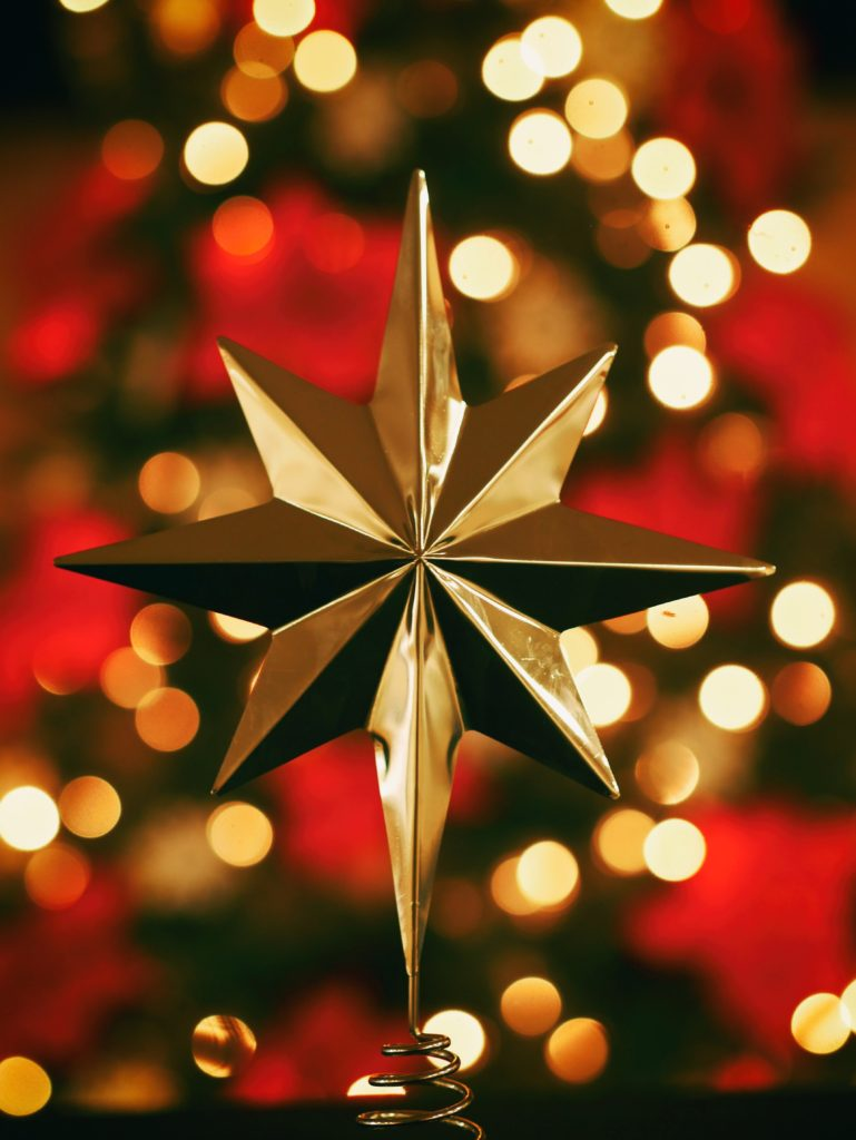 gold star top christmas tree ornament with sparkling lights in background